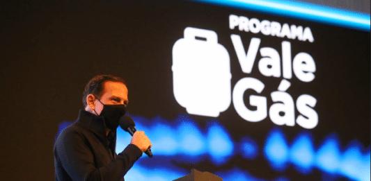 Dória com máscara de proteção preta falando no microfone no evento do programa Vale Gás