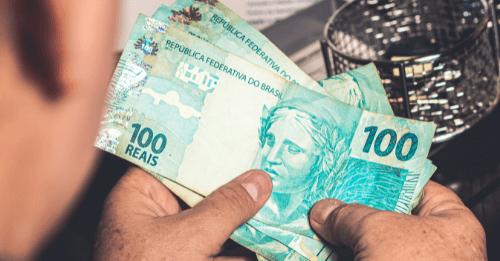 Homem conta notas de dinheiro do programa Acolhe Ribeirão