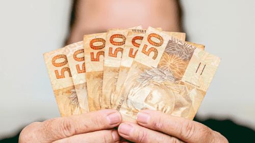 Mulher mostra notas de dinheiro do programa Acolhe Ribeirão