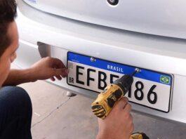 homem colocando placa em carro