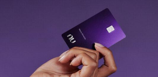 Uma mão feminina segurando o cartão do Nubank Ultravioleta