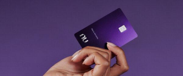 Uma mão feminina segurando o cartão Nubank Ultravioleta