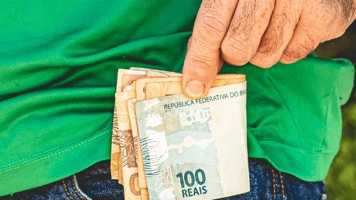 Mão masculina coloca notas de dinheiro do auxílio emergencial no bolso