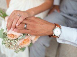 mão de um casal com alianças em cima de um buquê
