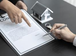 pessoa segurando contrato e outra assinando ao lado de uma casa em miniatura