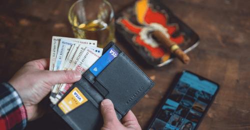 mão masculina segura carteira com dinheiro e cartões de crédito