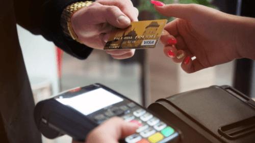 cartão de crédito é passado entre duas mãos