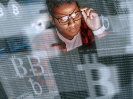 homem de óculos usando computador em uma montagem com símbolos do Bitcoin