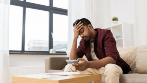 Homem preocupado sentado no sofá olhando para calculadora