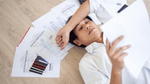 Homem deitado no chão lendo uma folha com várias contas espalhadas