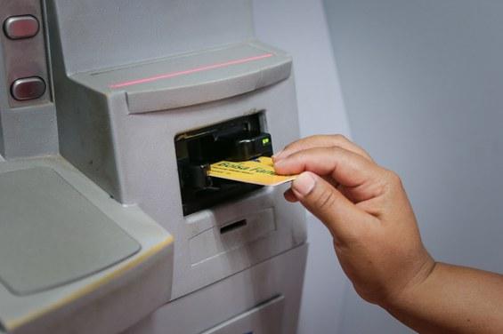 Mão feminina insere cartão do Bolsa Família no caixa eletrônico