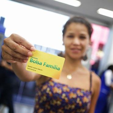 Mulher segura cartão do Bolsa Família