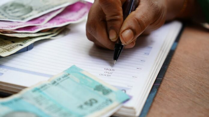 Mão masculina anota cálculos na agenda