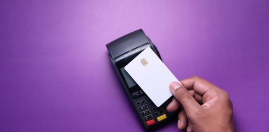 Homem segurando o cartão de aproximação Nubank com máquina de cartão em um fundo roxo