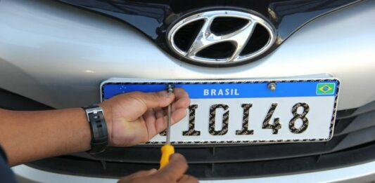 homem parafusando uma placa de carro