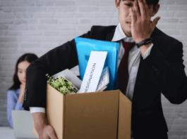 Homem engravatado sendo demitido segurando caixa com pertences