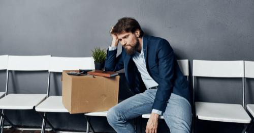 Homem desanimado sentado com o braço apoiado em uma caixa com seus pertences