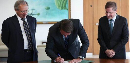 presidente Bolsonaro assinando a medida provisória ao lado de ministros