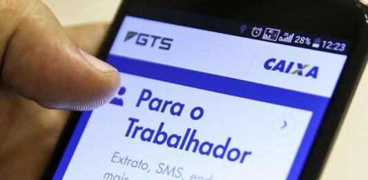 Mão segura celular aberto na tela inicial do aplicativo FGTS