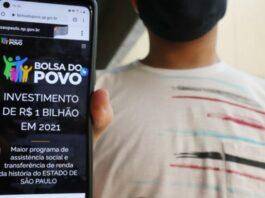 Menino mostra celular com tela aberta no site do Bolsa do Povo SP