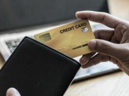 Mão masculina coloca um cartão de crédito sem limite dentro de uma carteira preta
