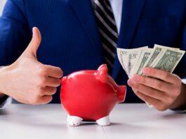 Empreendedor segura notas de dinheiro com a mão esquerda e faz sinal de positivo com a direita