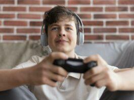 menino jogando videogame de fone