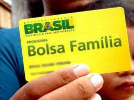 Mão masculina segura cartão do Bolsa Família