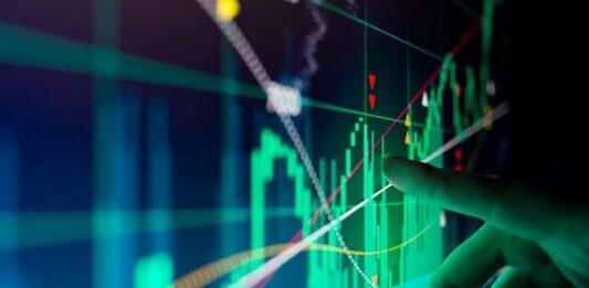 imagem de uma pessoa apontando para uma tela com gráficos de investimentos
