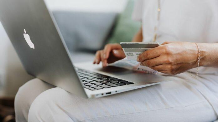 Mulher segura cartão de crédito na mão com apoiado notebook no colo
