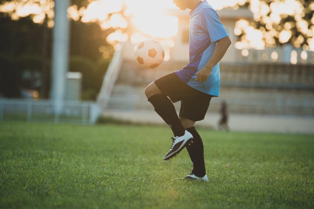 jogador de futebol fazendo embaixaidinhas em um campo