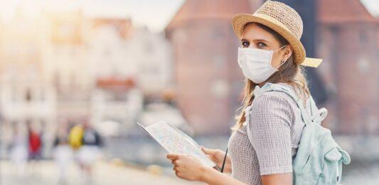 Mulher com máscara descartável no rosto um mapa turístico nas mãos