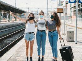 Três mulheres em uma estação de trem utilizam máscaras faciais e uma delas segura uma mala de viagem