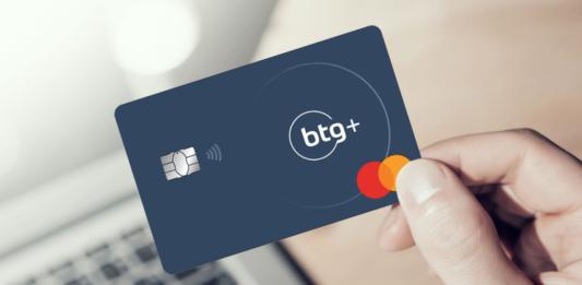 uma mão segurando o cartão do BTG+