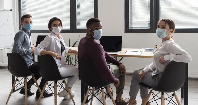 trabalhadores com máscara de proteção contra à Covid-19