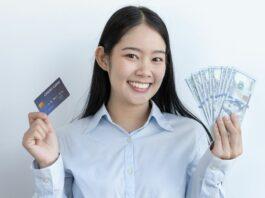 Mulher sorridente segura um cartão de crédito em uma das mãos e cédulas de dinheiro na outra