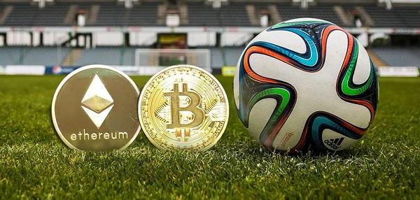 moedas digitais ao lado de uma bola de futel em um gramado