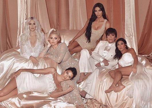 Irmãs Kardashian e Kris Jenner posam para foto em um sofá, todas vestidas de branco
