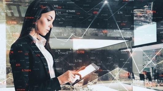 Mulher de terno olha para um tablet com gráficos de cotação de moedas no Forex
