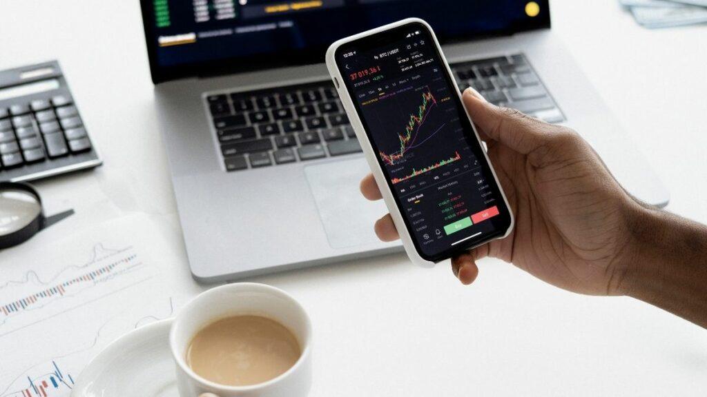 homem segura celular com gráfico que mostra oscilação da Bolsa de Valores