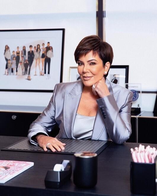 Kris Jenner Kardashian posa para foto sorrindo, sentada a uma mesa de escritório
