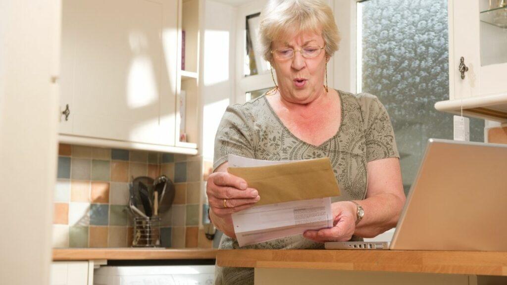 Mulher idosa olha assustada para um extrato bancário