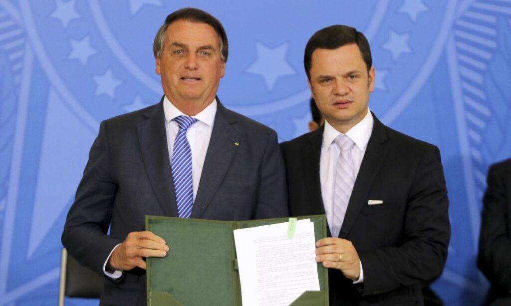 Presidente Jair Bolsonaro e ministro da Justiça, Anderson Torres, posam para foto segurando a medida provisória que cria o Habite Seguro
