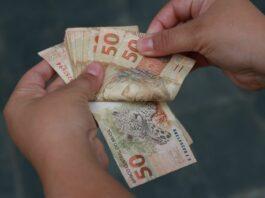 Homem conta notas de 50 reais na mão