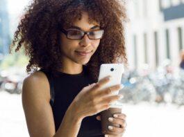 Menina com blusa preta segura celular nas mãos e olha para a tela sorrindo