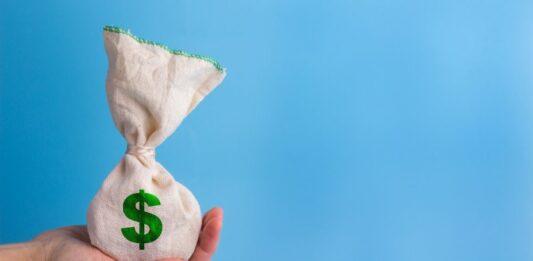 Uma mão segura um saco de dinheiro com o símbolo do cifrão