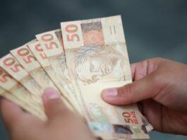 Pessoa com várias notas de 50 reais na mão