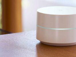 Um roteador Google Wifi na cor branca sobre uma mesa de madeira