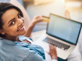 Mulher sorri em frente a um computado enquanto faz chama de de vídeo para reconhecer firma online